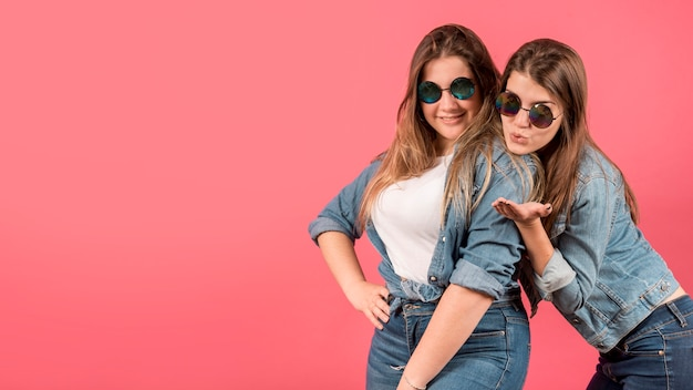 Portrait of two girls on red background