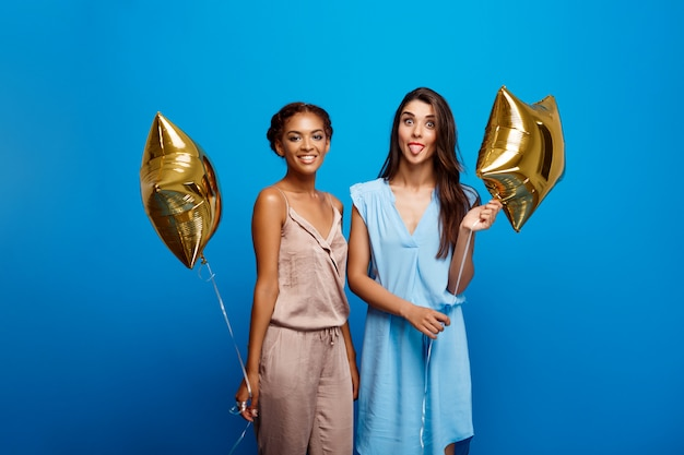 Portrait of two girls resting at party over blue wall