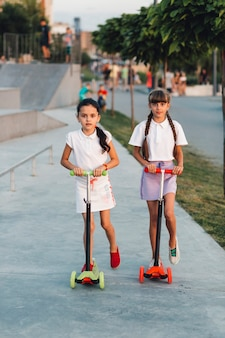 Portrait of two girls riding push scooter in the park