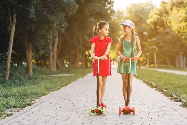 Portrait of two girls standing on push scooter looking at each other