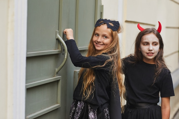 Portrait of two girls wearing halloween costumes knocking on doors and smiling  while trick or treating together