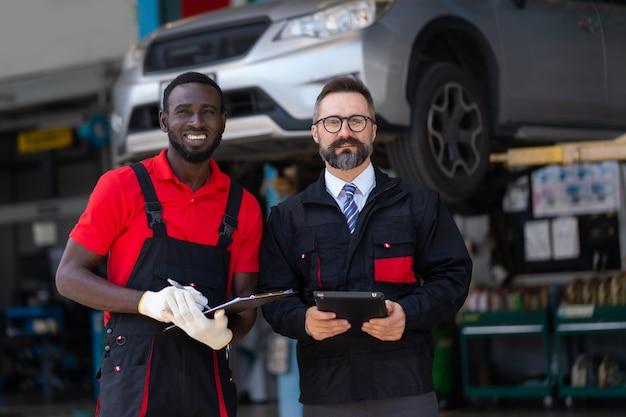 자동차 서비스에 함께 서 있는 제복을 입은 두 명의 잘생긴 자동차 정비공을 초상화. 블랙 라이브 문제. 흑인 남성과 백인 남자 사람들입니다.