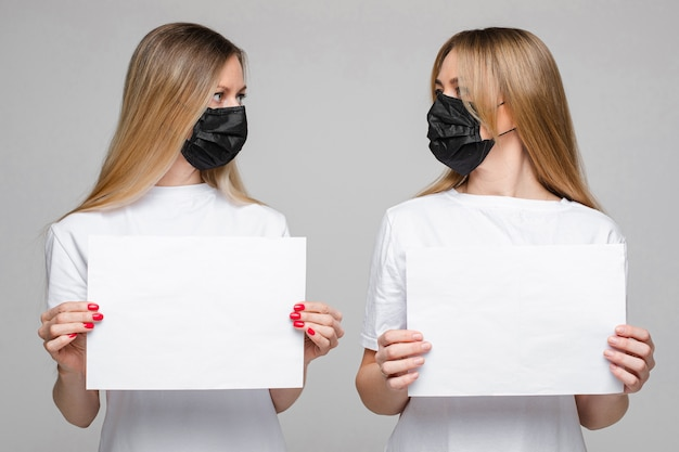 Portrait of two handsome girls with long fair hair and black medical mask on her face isolated