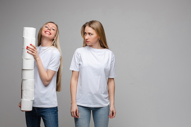 Portrait of two handsome girls with long fair hair, one of them holds a lot of toilet paper and other is offended isolated