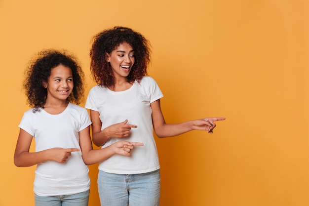 Portrait of a two happy afro american sisters pointing