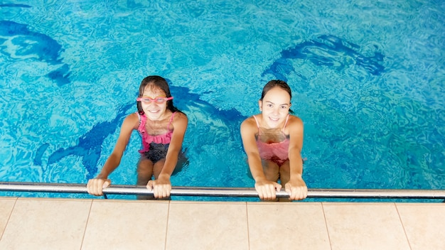 Portrait of two happy cheerful smiling teenage girls in the indoors swimming pool