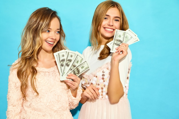 Portrait of two happy delighted blond women wearing summer clothes rejoicing win and holding cash money isolated over blue wall