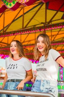 Portrait of two happy female friends at amusement park