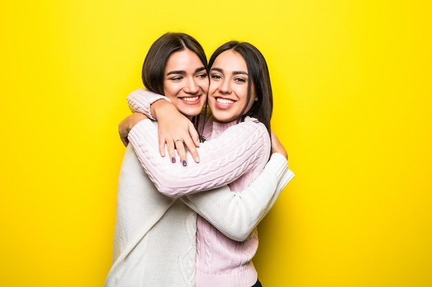 Portrait of two happy girls dressed in sweaters hugging isolated over yellow wall