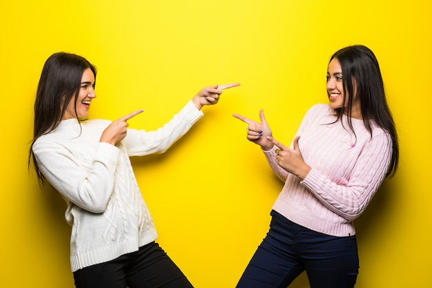 Portrait of two happy girls dressed in sweaters pointing fingers each other isolated over yellow wall