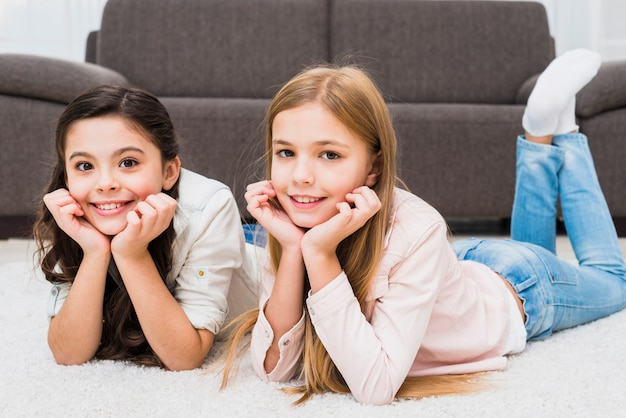 Portrait of two happy girls lying on white carpet in front of sofa