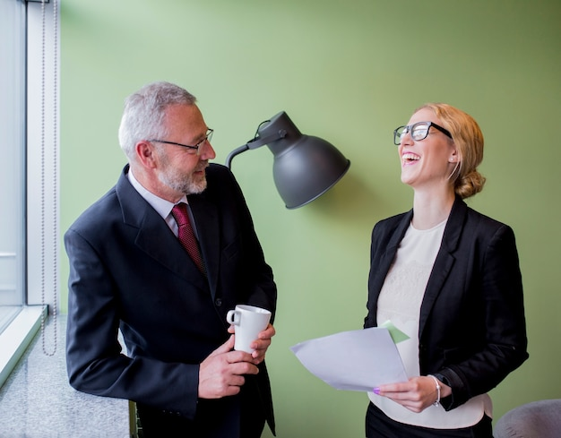 Portrait of two happy mature businessman and young businesswoman taking break