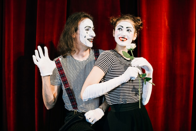 Portrait of two happy mime artist in front of red curtain