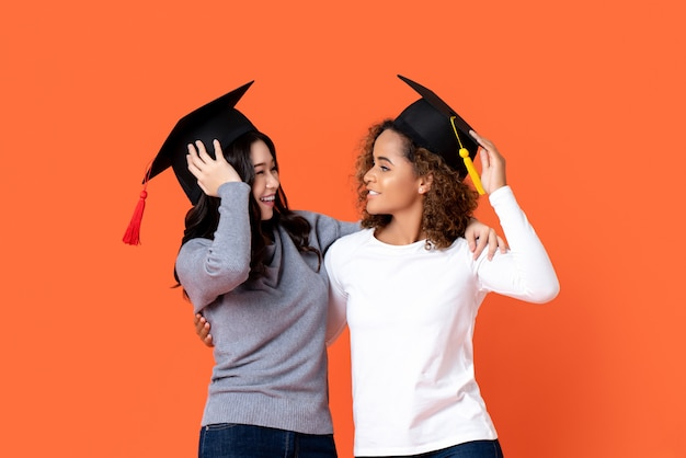 Portrait of two happy mixed-race women graduating holding there graduation caps looking at each other in orange isolated wall