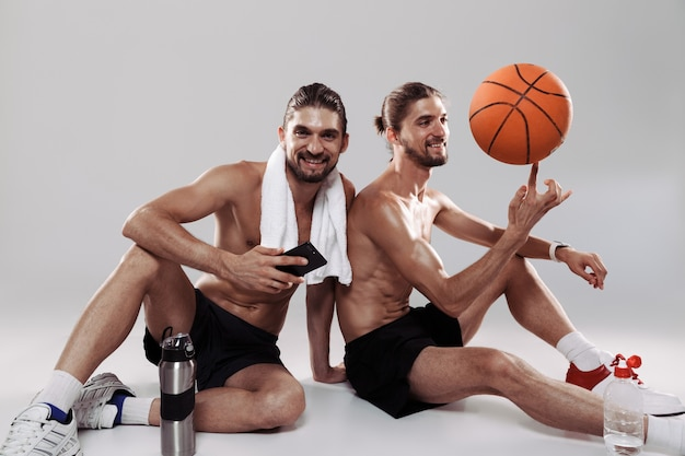 Portrait of a two happy muscular shirtless twin brothers