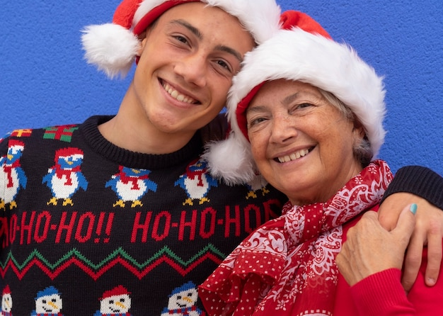 Portrait of two happy people, grandmother and grandson wearing santa hat and christmas sweater, hugging each other with love and smiling looking at camera. positive emotion and family concept