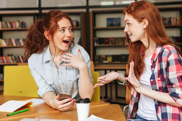 Portrait of a two happy teenage girls talking