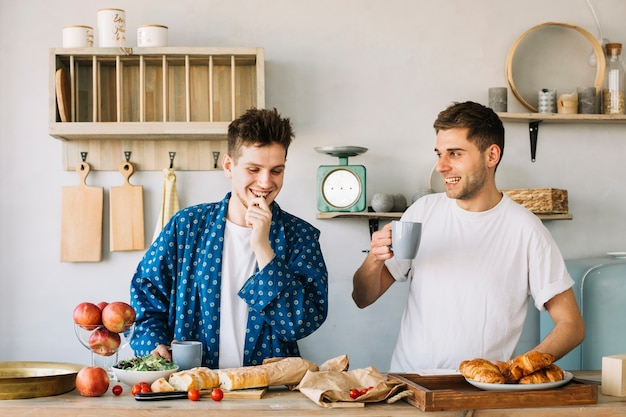 Portrait of two happy young man preparing breakfast in kitchen