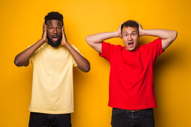 Portrait of a two happy young men cover ears isolated over yellow wall