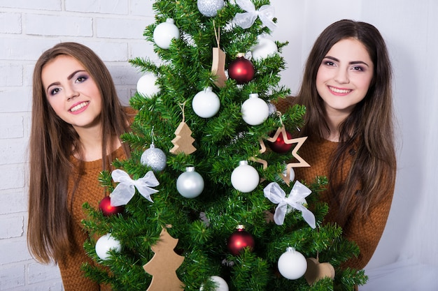 Portrait of two happy young women with decorated christmas tree at home