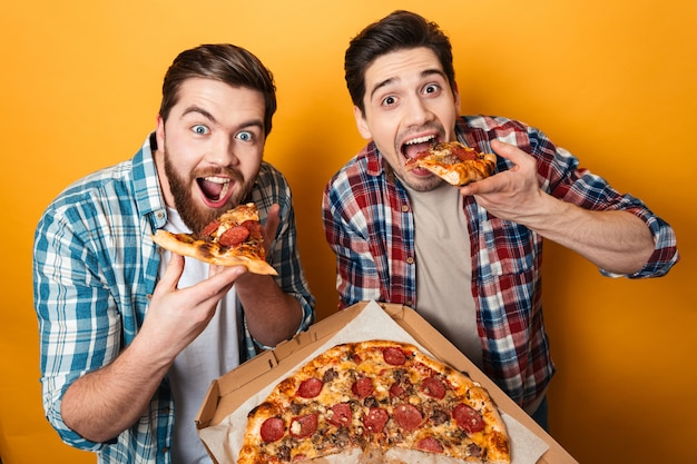 Portrait of a two hungry young men eating pizza
