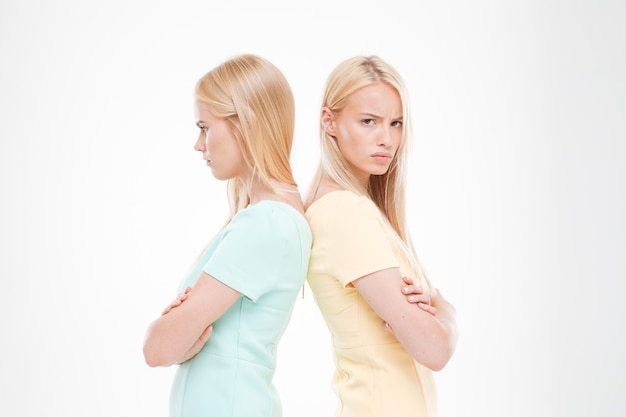 Portrait of two indignant girls standing back to each other with arms crossed isolated over white wall