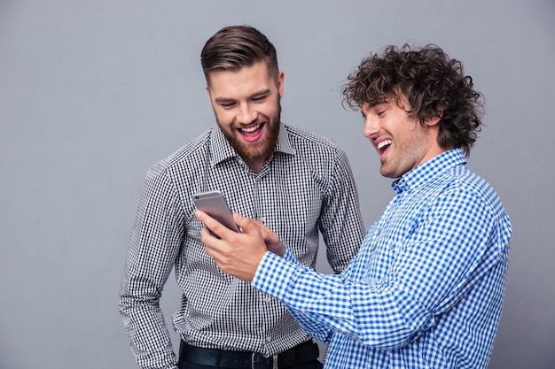 Portrait of a two laughing men using smartphone over gray wall