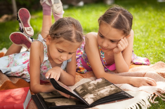Portrait of two little sisters looking photo album at park
