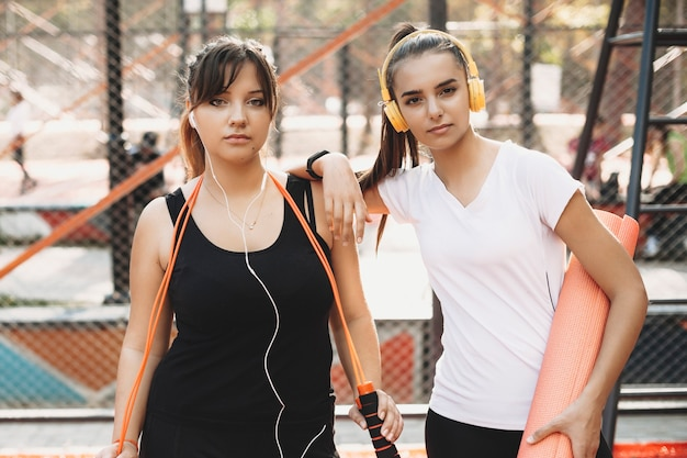 Portrait of two lovely girlfriend doing morning sport routine for losing weight in a sport park listening music looking at camera seriously.