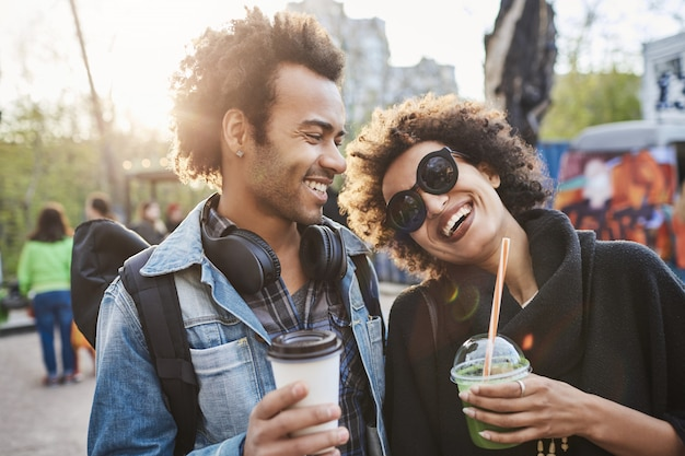 Portrait of two lovers with afro haircuts, strolling in park and drinking coffee while talking and enjoying spending time at food festival.
