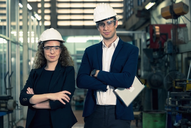 Portrait of two machinists is standing with confident with   safety helmet in front the glass wall of industry factory.