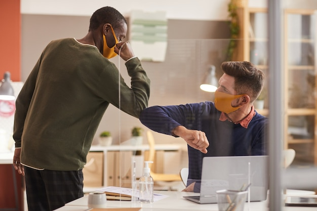 Portrait of two men touching elbows as contactless greeting in office