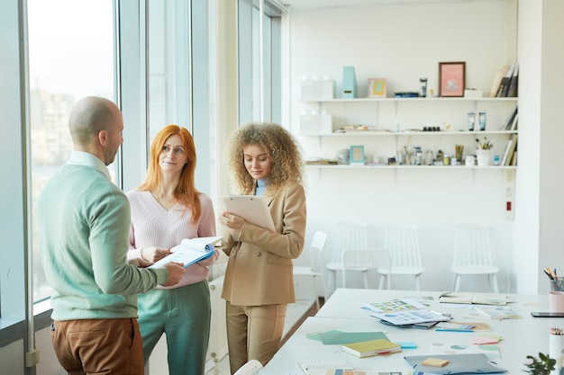 Portrait of two modern businesswomen talking to mature manager while standing in modern office, copy space