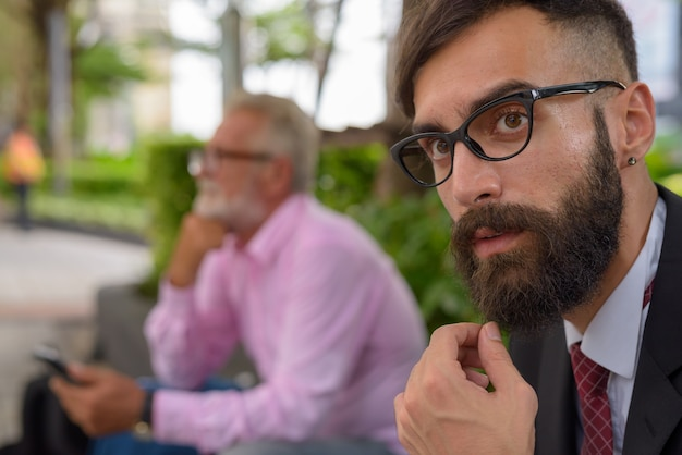 Portrait of two multi ethnic bearded businessmen together around the city of bangkok