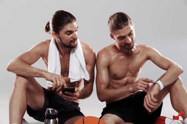 Portrait of a two muscular shirtless twin brothers