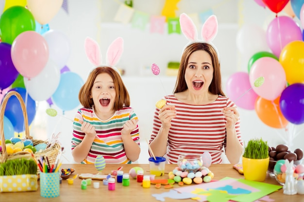Portrait of two nice attractive ecstatic crazy creative cheerful cheery girls small little pre-teen sister wearing bunny ears having fun making craft in white light interior room house
