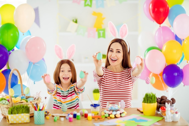Portrait of two nice attractive glad creative cheerful cheery girls small little pre-teen daughter wearing bunny ears showing decorative eggs on sticks in white light interior room house