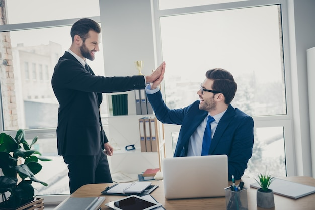 Portrait of two nice attractive handsome confident cheerful cheery men lawyer attorney economist financier giving high five good job done motivation in light white interior workplace workstation