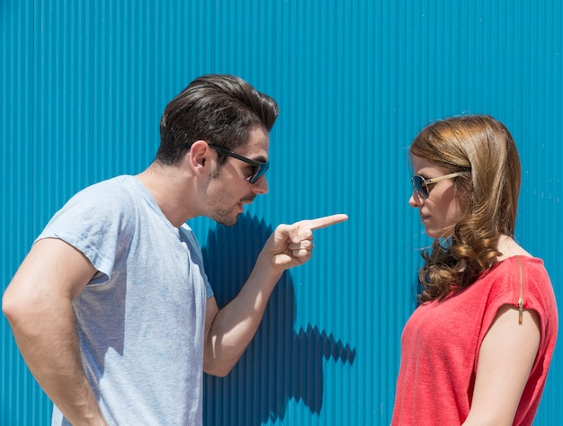 Portrait of two people, man and woman , woman to man pointing fingers, blaming her for the problem. difficulties in marriage concept . negative emotions