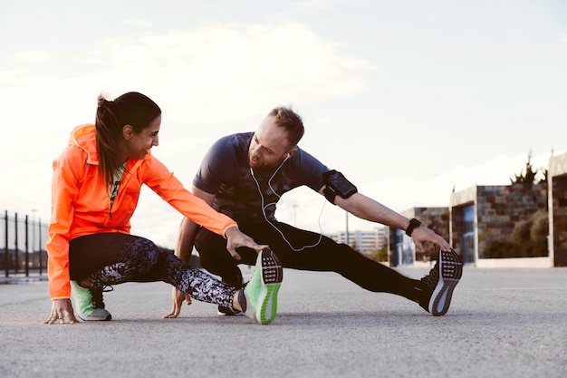 Portrait of two people stretching outdoors