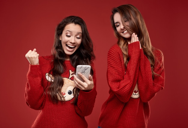 Portrait of two pretty crazy best friends in fashion cozy winter sweater screaming for joy while looking at the phone