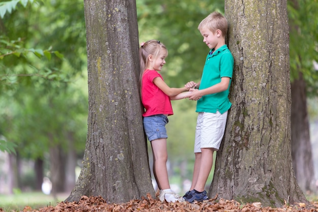 Portrait of two pretty cute children boy and girl standing near big tree trunk in summer park outdoors.
