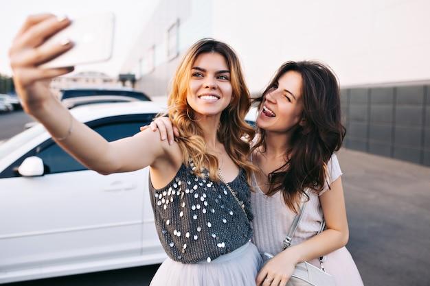 駐車場で楽しい2つのかわいい女の子の肖像画。自撮りを作るブロンドの女の子、舌を示す近くのブルネット、彼らは笑っています。