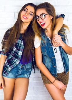 Portrait of two pretty teen girlfriends smiling  and hugging each other