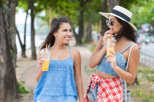 Portrait of two pretty woman drinking fresh juice while walk in park young girls tourists
