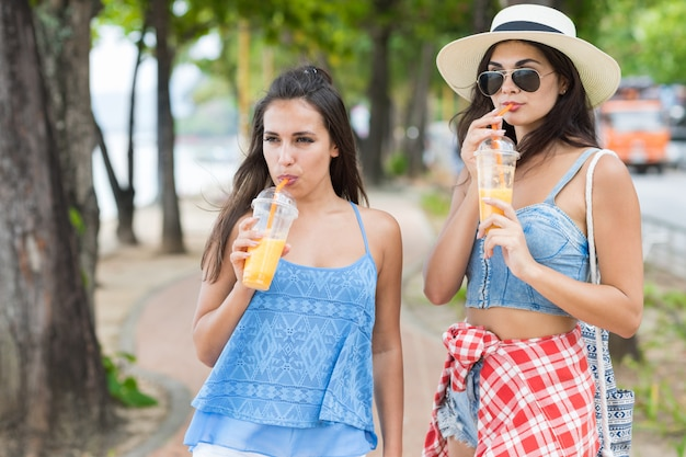 Portrait of two pretty woman drinking fresh juice while walk