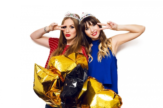 Portrait of two pretty women with bright party balloons