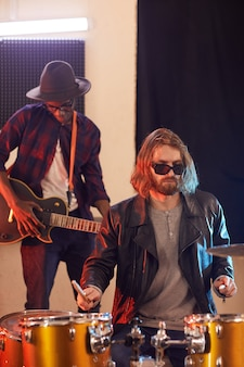 Portrait of two rock band musicians rehearsing in music studio