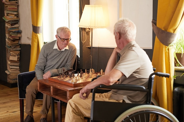 Portrait of two senior men playing chess and enjoying activities in cozy nursing home