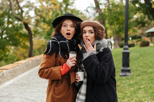 Portrait of two shocked girls dressed in autumn clothes